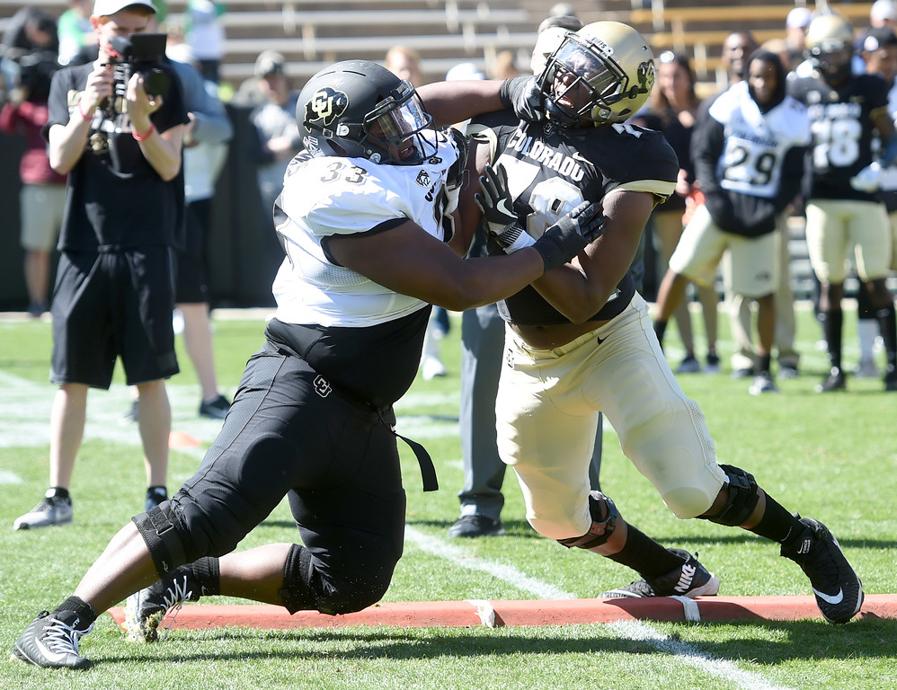 . Javier Edwards, left, and William Sherman, battle during the CU Spring football festivities on Saturday.  Cliff Grassmick  Photographer  March 17, 2018