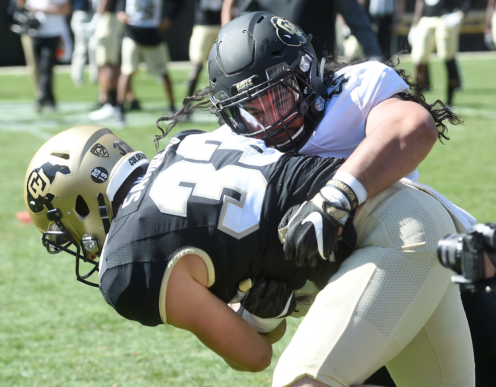 . Nu\'umotu Falo, Jr, tackles Chase Sanders during the CU Spring football festivities on Saturday.  Cliff Grassmick  Photographer  March 17, 2018