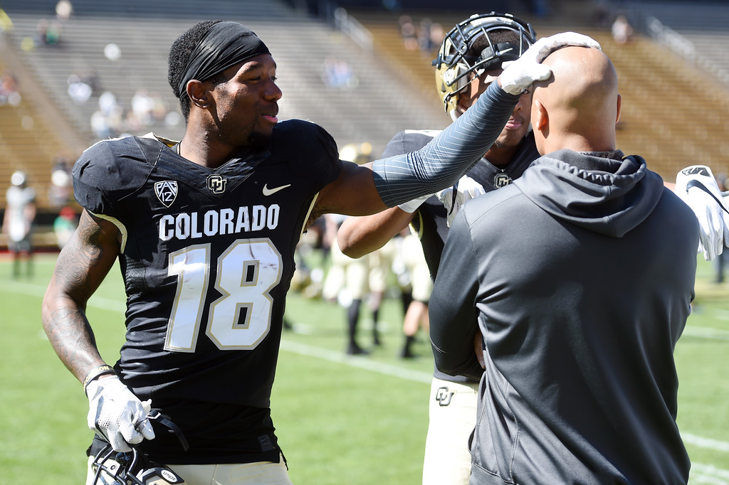 . Tony Brown rubs the head of Drew Wilson during the CU Spring football festivities on Saturday.  Cliff Grassmick  Photographer  March 17, 2018
