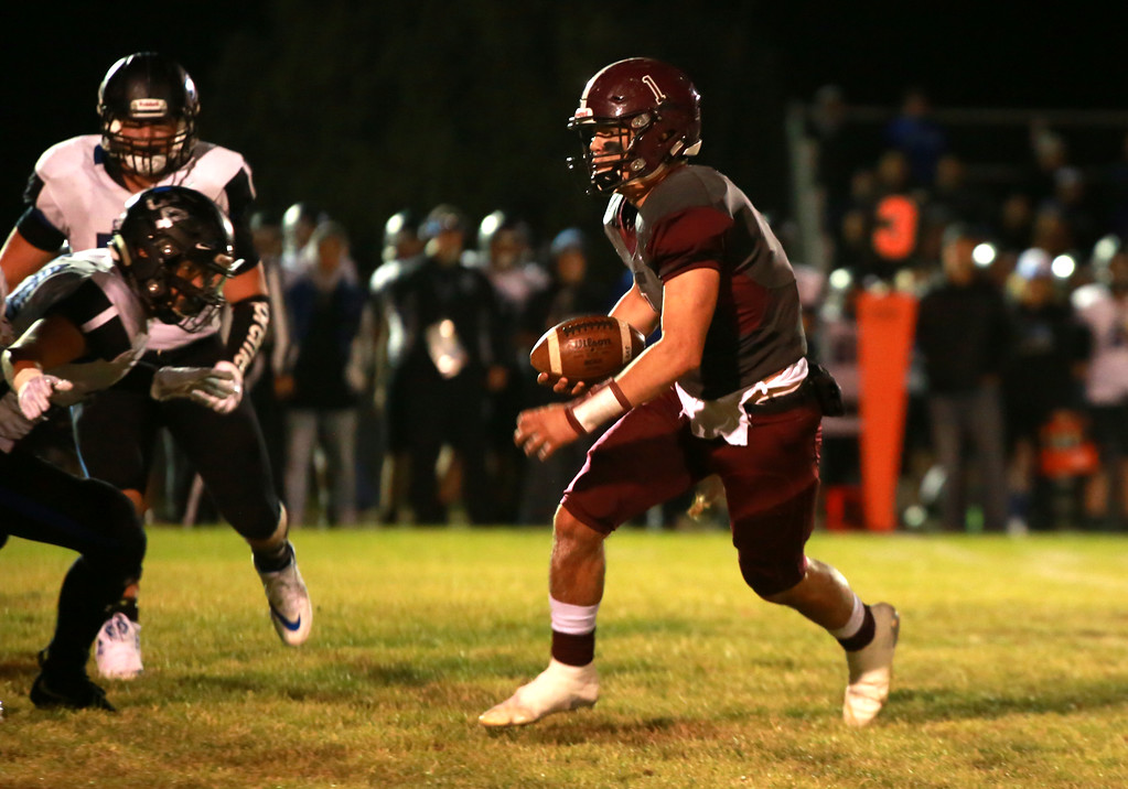 . Berthoud\'s (1) Jake Lozinski runs with the ball as Resurection Christian\'s (34) Daniel Kelley goes for the tackle at their game at Berthoud High School on Sept. 28, 21018 in Berthoud. Photo by Taelyn Livingston/ Loveland Reporter-Herald