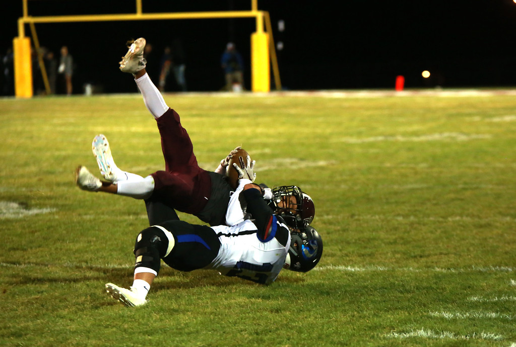 . Berthoud\'s (21) Miguel Sarmiento catches a pass as Resurection Christian\'s (13) Alex Riedel tackles him at their game at Berthoud High School on Sept. 28, 21018 in Berthoud. Photo by Taelyn Livingston/ Loveland Reporter-Herald