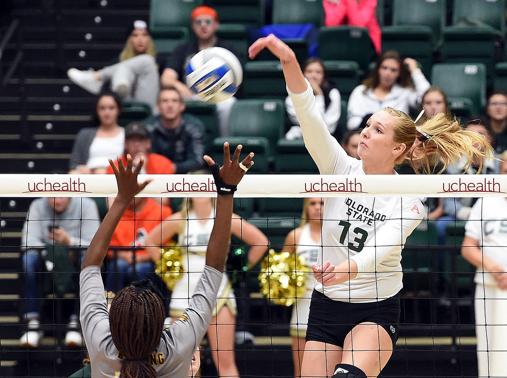 . Colorado State\'s Kirstie Hillyer spikes the ball as Wyoming\'s Reed Copelan tries to block during their game on Tuesday, Oct. 30, 2018, at Moby Arena in Fort Collins.  (Photo by Jenny Sparks/Loveland Reporter-Herald)