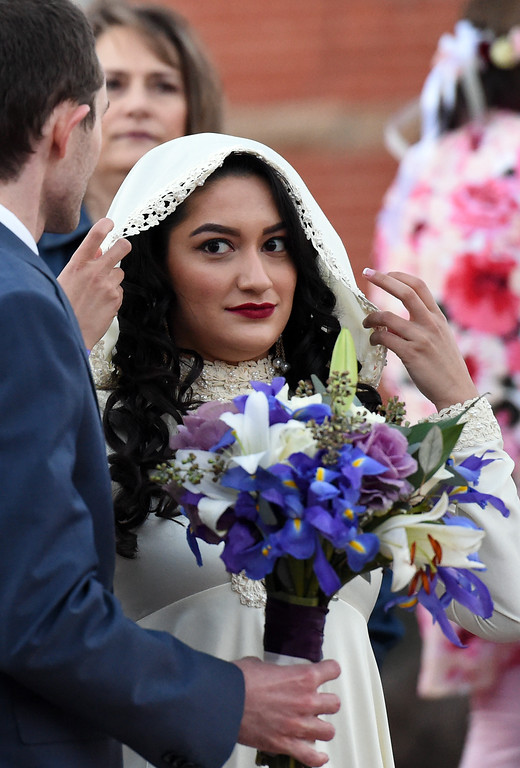 . Kristen Overheim adjusts her veil as she stands next to her groom, John Overheim during a group wedding ceremony Wednesday, Feb. 14, 2018, at Foote Lagoon in downtown Loveland.  (Photo by Jenny Sparks/Loveland Reporter-Herald)