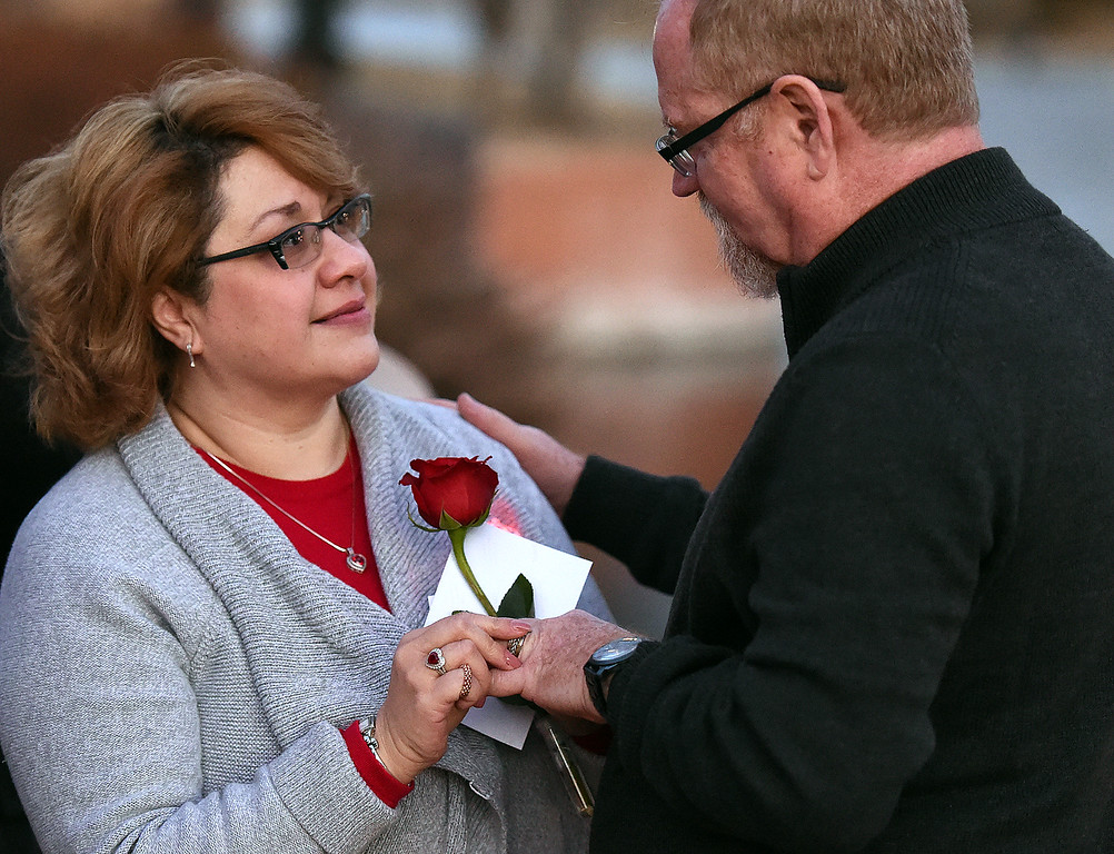 . Frankie Tallent, left, put the ring on her husband, Darren Tallent\'s finger while renewing their vows during a group wedding ceremony Wednesday, Feb. 14, 2018, at Foote Lagoon in downtown Loveland. TheTallents have been married 16 years. Eleven couples married and 12 renewed their vows. (Photo by Jenny Sparks/Loveland Reporter-Herald)