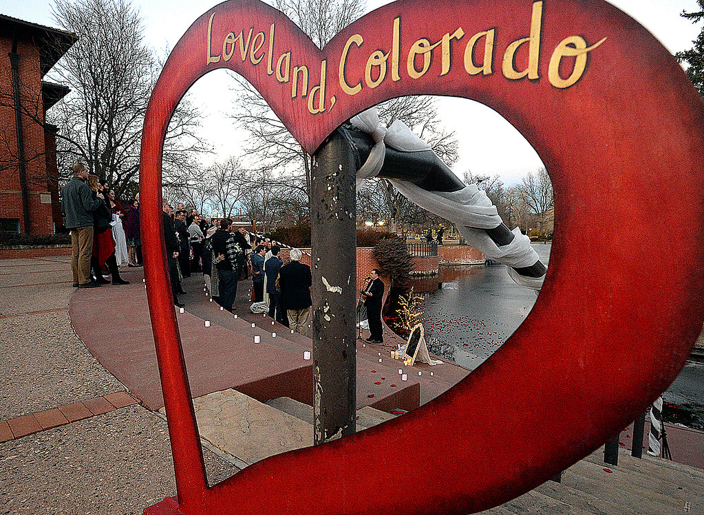 . Brides and grooms getting married are framed in a heart during a group wedding ceremony Wednesday, Feb. 14, 2018, at Foote Lagoon in downtown Loveland. Eleven couples married and 12 renewed their vows. (Photo by Jenny Sparks/Loveland Reporter-Herald)