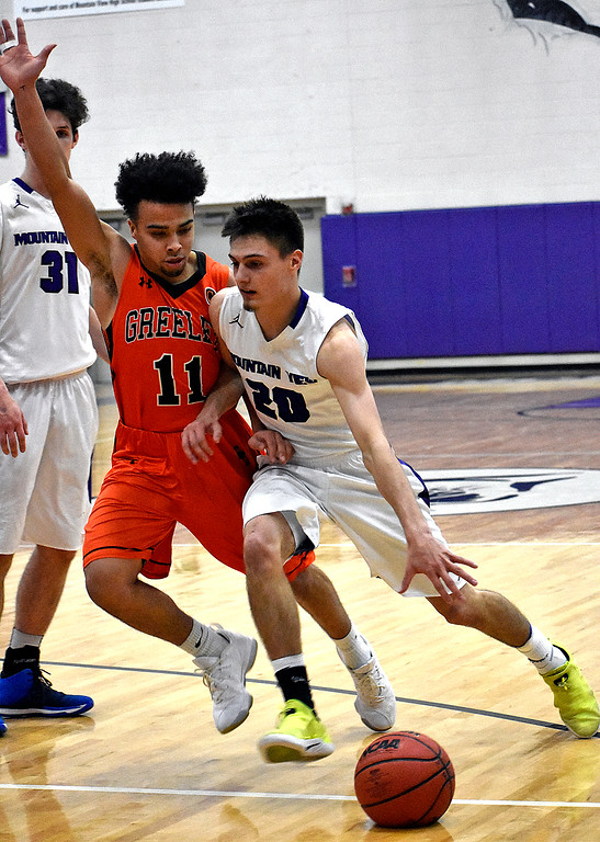 . Mountain View\'s (20) Brexton Butcher charges his way through Greeley\'s (11) Xavier Bonham\'s block during their game on Wednesday, Feb. 14, 2018 at Mountain View High School in Loveland. Photo by Thieng Mai/Loveland Reporter-Herald.