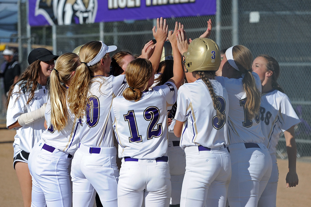 . Holy Family teammates surround Erin Caviness after her home run during a game Tuesday, September, 11, 2018 at Holy Family High School in Broomfield, Colorado. (Sean Star/Loveland Reporter-Herald)