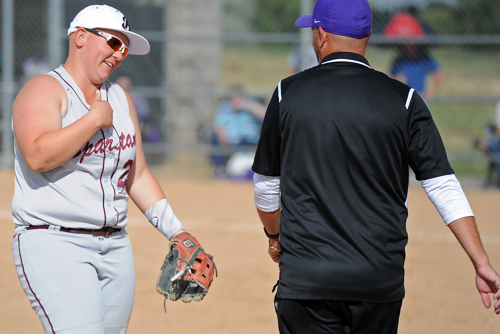 . Berthoud\'s Ashlynn Balliet shares a laugh with Holy Family\'s third base coach during a game Tuesday, September, 11, 2018 at Holy Family High School in Broomfield, Colorado. (Sean Star/Loveland Reporter-Herald)