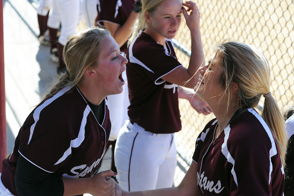 . Berthoud\'s Sarah Jorissen, left, celebrates in the dugout with Carly Rafferty during the first day of the 4A state softball tournament on Friday, Oct. 19, 2018 at Aurora Sports Park. (Sean Star/Loveland Reporter-Herald)