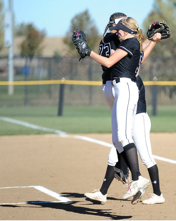 . Mountain View\'s Harley Duke and RaLeigh Basart bump shoulders during the first day of the 4A state softball tournament on Friday, Oct. 19, 2018 at Aurora Sports Park. (Sean Star/Loveland Reporter-Herald)