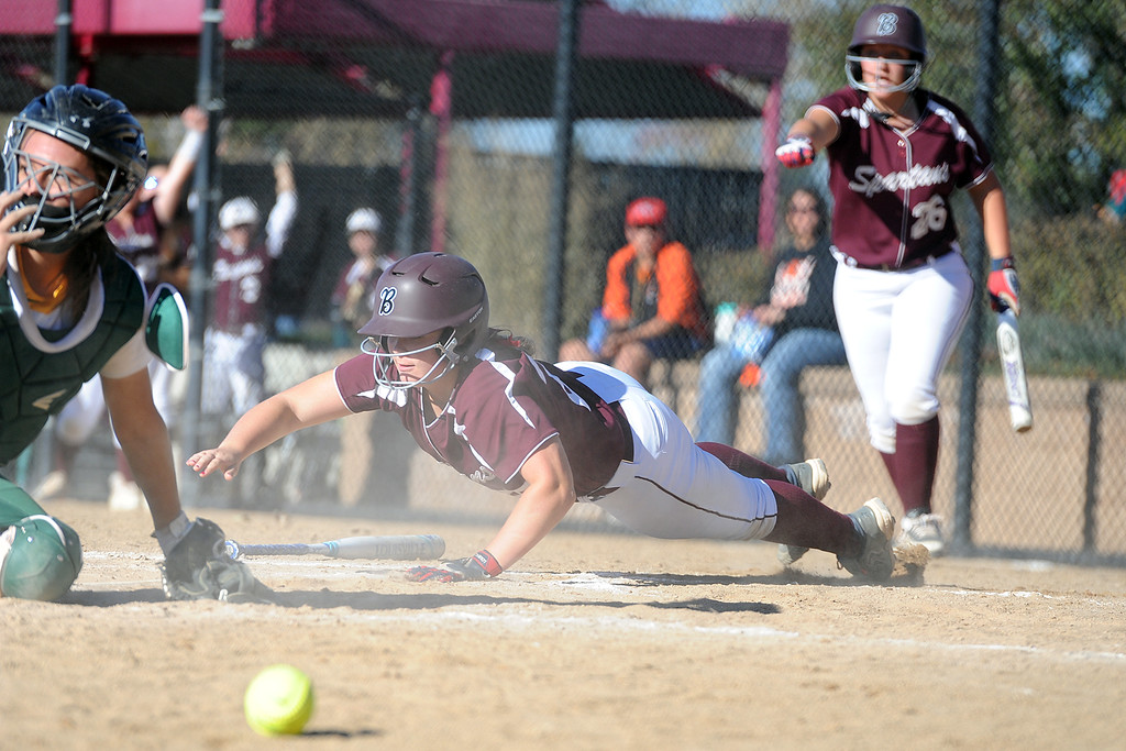 . Berthoud\'s Sarah Jorissen dives to touch home as Pueblo County\'s catcher searches for the ball during the first day of the 4A state softball tournament on Friday, Oct. 19, 2018 at Aurora Sports Park. (Sean Star/Loveland Reporter-Herald)