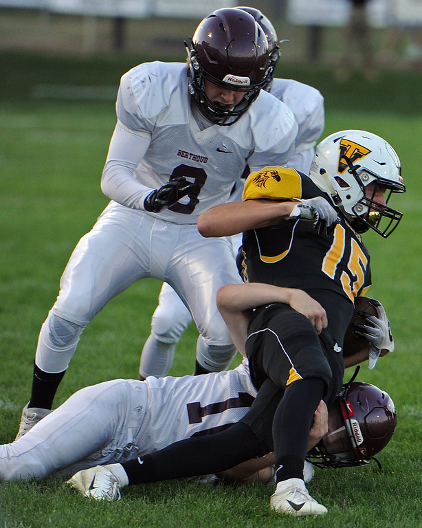 . Thompson Valley\'s Trey Kreikemeier (15) is tackled by Berthoud\'s Brennen Garvin (bottom) and Grant Vomacka (8) during a game Friday, Sept. 14, 2018 at Patterson Stadium in Loveland, Colorado. (Sean Star/Loveland Reporter-Herald)