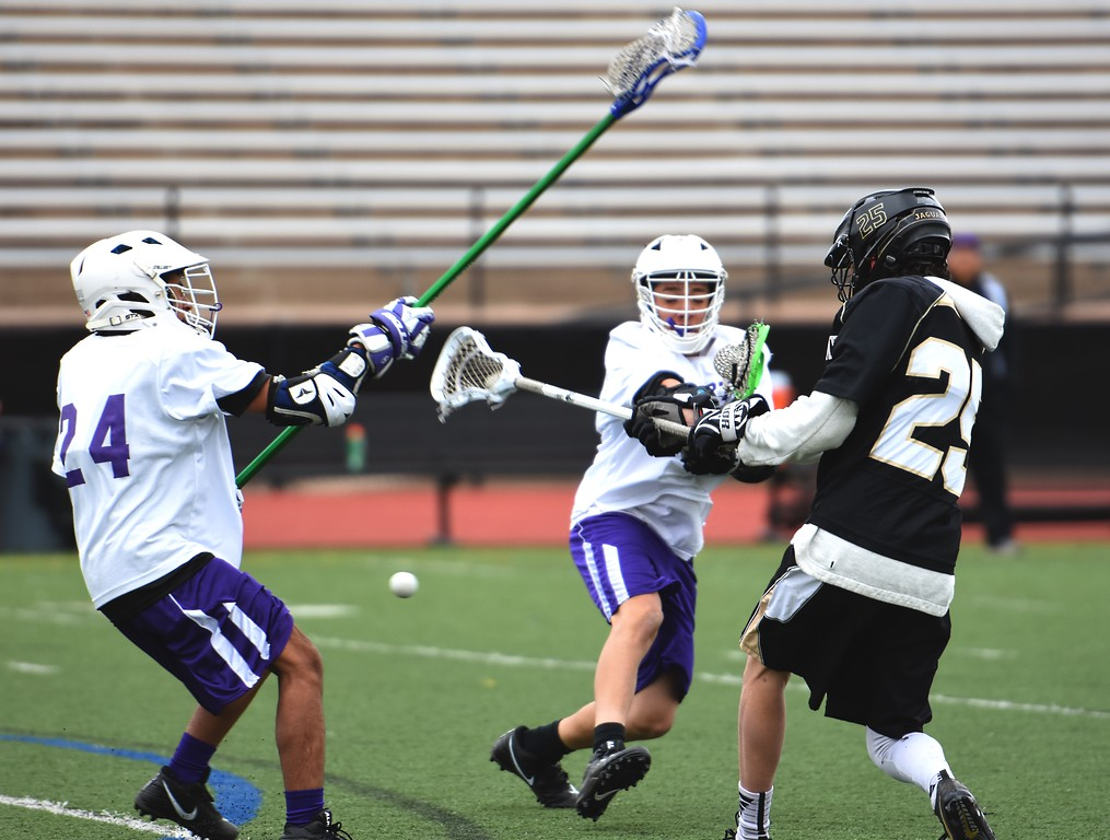 . Jefferson Academy\'s Isaac Mercurio shoots through a pair of defenders during the Jaguars\' game against Denver North on Friday, April 13, at All-City Stadium in Denver.