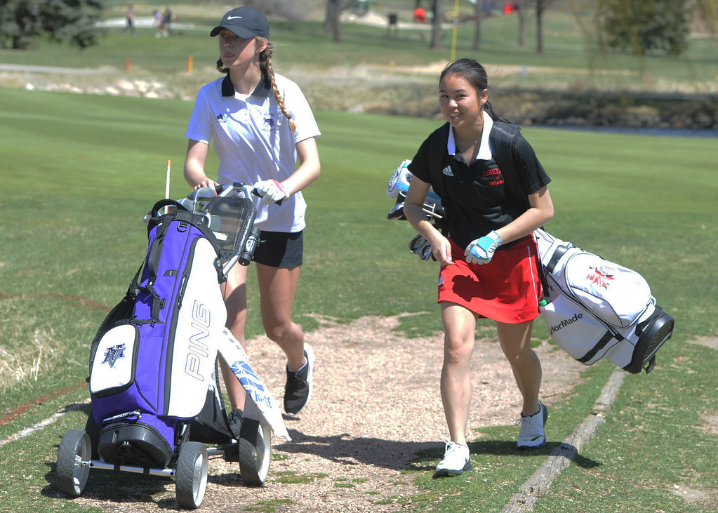 . Mountain View\'s Isabella Romero, left, and Loveland\'s Casey Bradley walk off the 14th green during the Loveland Invitational on Wednesday, April 11, 2018 at the Olde Course at Loveland. (Sean Star/Loveland Reporter-Herald)