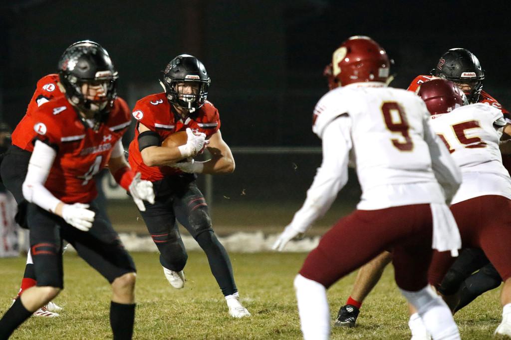 . Loveland�s Zach Weinmaster (3) runs the ball while Cody Rakowsky (4) blocks him from Ponderosa�s Jack Rickard (9) on Friday, Nov. 10, 2017, at Patterson Stadium in Loveland. (Photo by Lauren Cordova/Loveland Reporter-Herald)