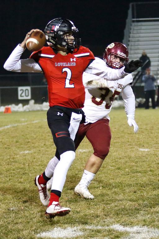 . Loveland�s Riley Kinney (2) reaches back to pass the ball before Ponderosa�s Ethan Waite (35) can sack him  on Friday, Nov. 10, 2017, at Patterson Stadium in Loveland. (Photo by Lauren Cordova/Loveland Reporter-Herald)
