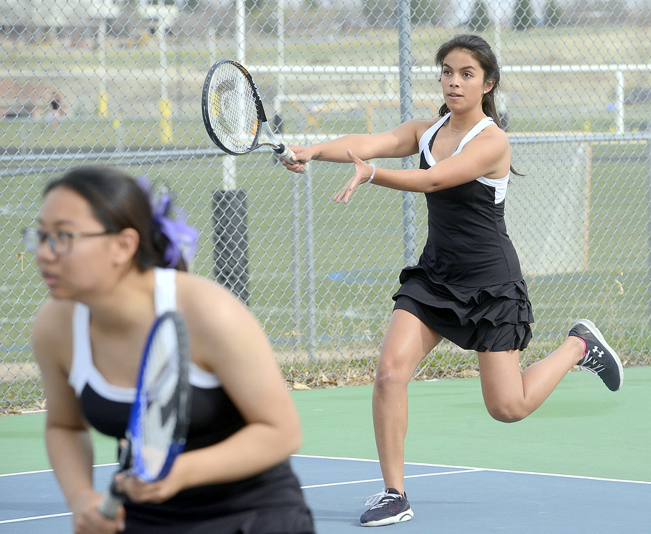 . Mountain View No. 4 doubles player Janet Perez comes up to return a serve as partner Angel Yu watches the movements on the other side of the net during Thursday\'s match at Thompson Valley. (Mike Brohard/Loveland Reporter-Herald)