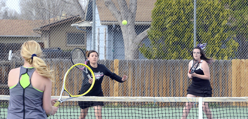 . Mountain View\'s Kali Kelly returns a shot in the No. 1 doubles match as her partner, Dusty Berglund, and Thompson Valley\'s Danielle Sobraske look on during  Thursday\'s match at the TVHS courts. (Mike Brohard/Loveland Reporter-Herald)