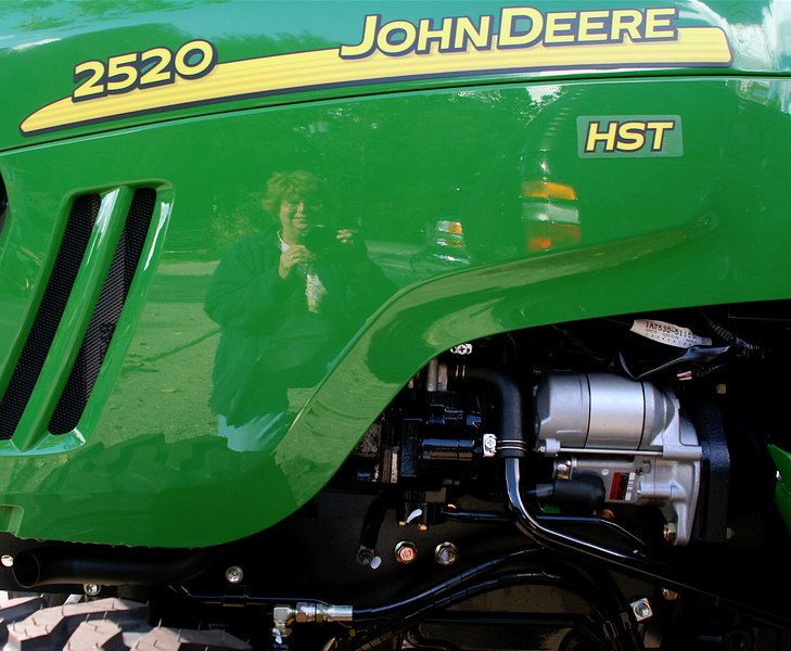 """SEPTEMBER 29TH<br /> <br />             PICTURE YOURSELF IN A JOHN DEERE<br /> <br />  This actually took a while to achieve. Either the light was off or the angle wasn't good. I actually knelt there, focused then moved the camera so you could see my face...geeze....what I won't do for DP! <br /> Ok, so I have been cooped up in my house too long...Got a little corny... see gallery for photo #2 <a href=""""http://mom4squirrels.smugmug.com/gallery/1775470/1/98808796"""">http://mom4squirrels.smugmug.com/gallery/1775470/1/98808796</a>"""