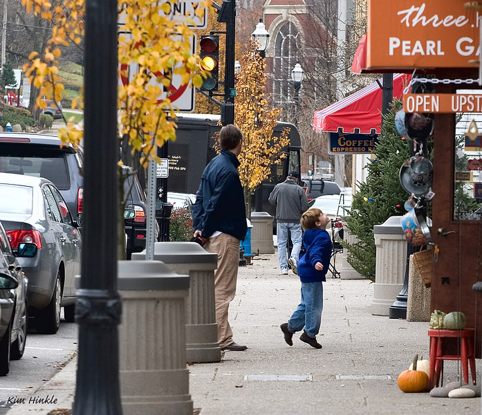 "November 14th<br /> <br /> WAITING FOR MOM..<br /> <br /> This is a scene from a quaint town near us called Chagrin Falls.  While photographing the last of the roses in bloom in town, I spotted this little boy and his dad waiting  for Mom to come out of the store.  Here he seems to be trying to get a better view of the decorations that are going up all over for Christmas.  <br /> Here is the link to the other two I took...this one is the best IMO:<br />   <a href=""http://mom4squirrels.smugmug.com/gallery/1775470/1/110418688/Large"">http://mom4squirrels.smugmug.com/gallery/1775470/1/110418688/Large</a>"