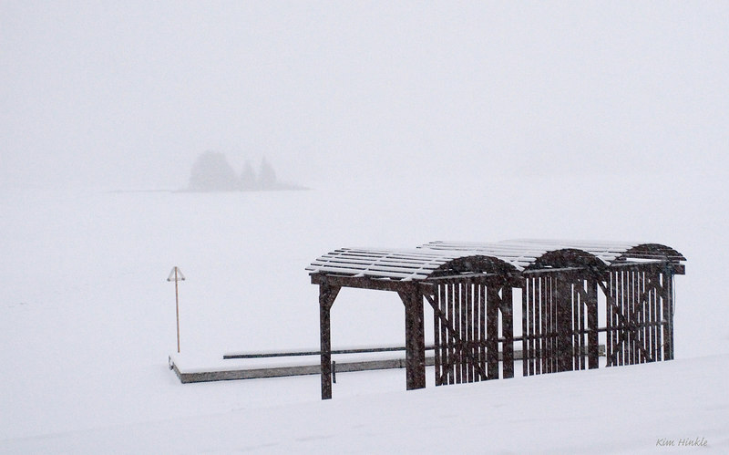 January 25th<br /> <br /> CABANAS IN A BLIZZARD<br /> <br /> Amazingly what you are looking at are the empty cabanas that sit on the beach down hill from the cottages we stayed in in Canada.  In front of them is the beach, then the dock for canoes and paddle boats.  The rest is Oxtongue Lake...and an island quite aways out from shore. The lake was totally frozen over.  Snow mobiles were racing across the icy surface, and a portion of the shoreline near this was being watered down..and then scraped for ice skating.  We awoke to this white out on the morning of our departure for home.  (Winter sports are a big part of the local livelyhood up there...so folks were quite happy to see the cold and snow return.