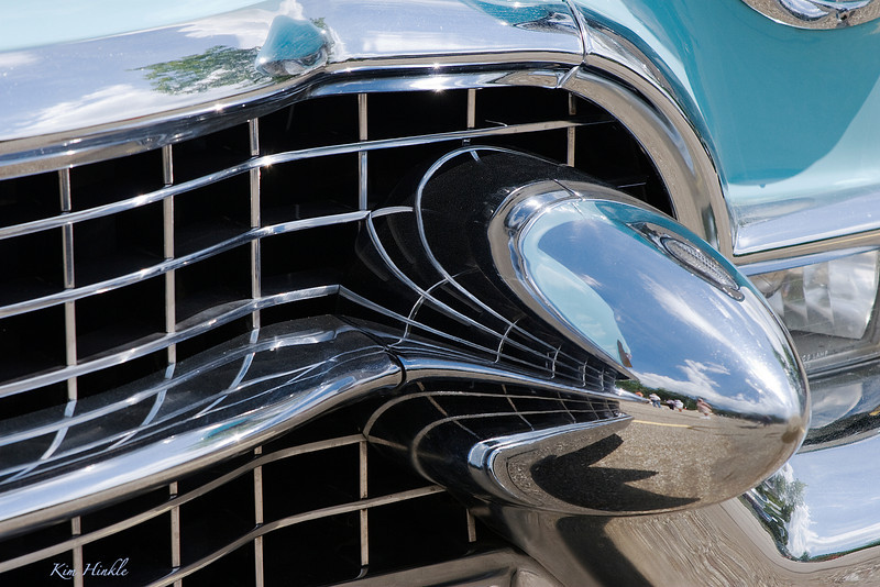 "August 11th<br /> <br /> CADILLAC BUMPER<br /> <br /> Seizing the opportunity to try shooting things I don't normally attempt, here is my best ""abstract"" from the car show.  It is the bumper of a turquoise convertible (Don't know the year...but Carol will)  I loved the reflections and the grill.  Visualizing interesting angles was not easy...my hat is off to all of you who take such great images at the car shows!"