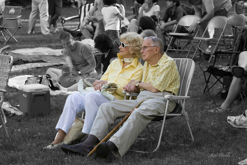 """July 15th<br /> <br /> """"A TOUCHING MOMENT""""<br /> <br /> Taken at a free concert at the Cleveland Metroparks.  The hand-holding closeness of this couple really touched me and I snapped this moment in time of them.  Here is the color version, but I wanted to single them out with SC.  Do you think it enhances the image?  ...of course this is the result of about 3 hours of work...wow, sc isn't as easy as you'd think!<br /> <br /> <a href=""""http://mom4squirrels.smugmug.com/gallery/1775470_4zZxA/1/331680677_VtKvp#331679491_t2TxS"""">http://mom4squirrels.smugmug.com/gallery/1775470_4zZxA/1/331680677_VtKvp#331679491_t2TxS</a><br /> <br /> (After taking 130  mediocre images of people, I realize that people photos are WAY out of my comfort zone and artistic eye.  My children photos were better (you'll see some posted later), but folks in a crowd lacked the feel that I was searching for...I take my hat off to Hillary, Carolyn and all of you who photograph people so well!!"""