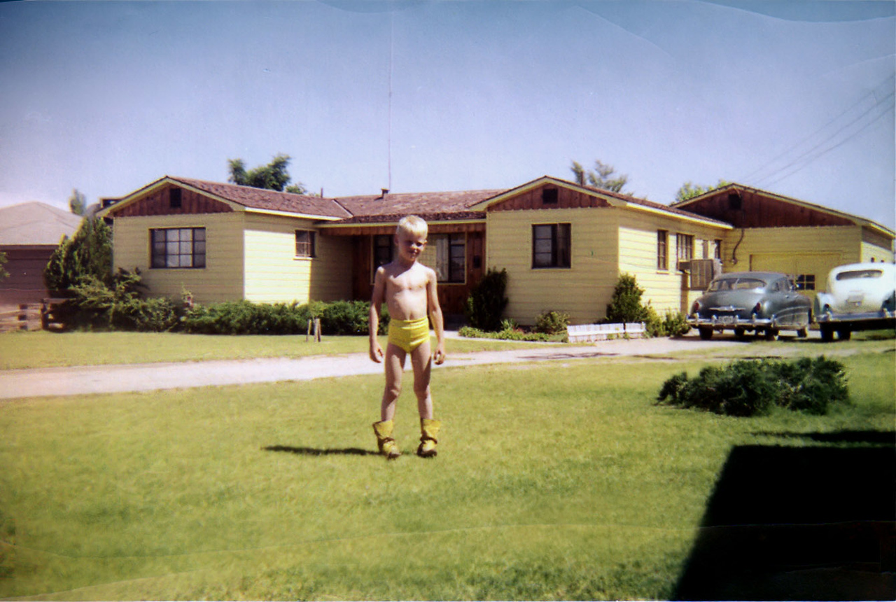 1-18-11  (Day late and a dollar short on the childhood challenge.)<br /> <br /> I think this is around '55 or '56. Dig those yellow duds with matching boots. If my memory serves me I think I also had a beanie with a propeller on it that was multicolored and I usually wore it with this outfit. My house was behind me. We had a 1950 Hudson Commodore and a Henry J in the driveway. Our house was at the end of N. James St in Carlsbad, NM and butted up to a field that led to Tansil Dam and the power plant about 100 yds back. <br /> <br /> I have many scary and pleasant memories there. Scary at night with weird noises coming from the river below. Scary when crossing the river right below the outflow tube and the water rising quickly and washing you down the river. I think the workers in the power plant used to watch and turn it on just to scare the crap out of us for a laugh, I swear it. Finding and bringing home baby rattlesnakes in a tin can and my mother going balistic, turtles, starfish, etc. Bull whip snakes running across the yard as though they were chasing you.<br /> <br /> I used to wear out a deck of cards a week on my bicycle. Miss the hell out of kick the can and Olly olly aux in free. Enough already.<br /> <br /> Sorry for turning in a late assignment, just didn't catch the notice.