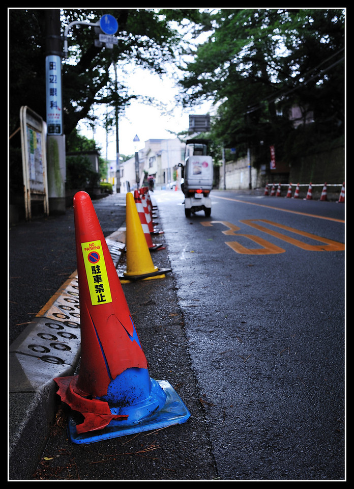 Day 193 July 12<br /> This is a late afternoon shot in light drizzle. The cones are here to keep taxi drivers from parking in the bus loading zone. This is just around the corner from our house, and we used to be able to catch a taxi here 24/7, but no more...