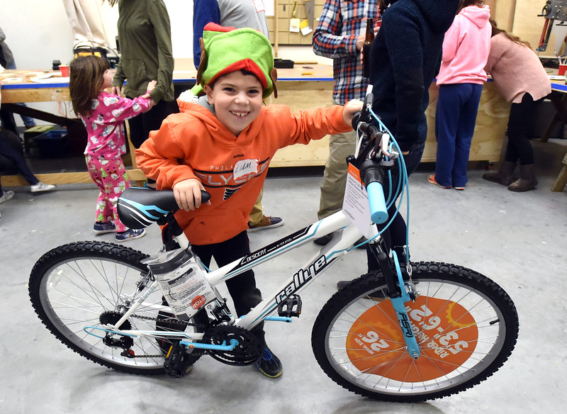 PETE  BANNAN-DIGITAL FIRST MEDIA    <br /> Liam Scully,7, of West Chester holds the bicycle he helped build with his father, Mick Scully as part of the Pine Street Carpenters'  100 bike build workshop in West Goshen Thursday Dec. 8.