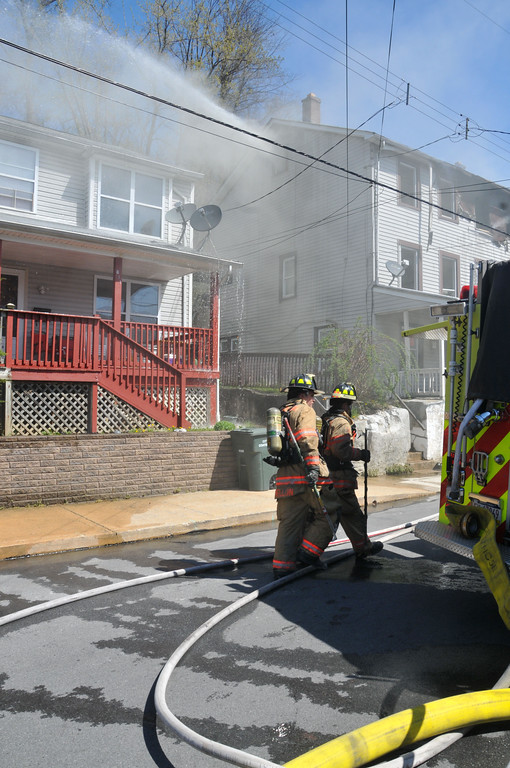 . PETE  BANNAN-DIGITAL FIRST MEDIA        Firefighters shoot smoke from a window to remove smoke at a house fire on the 600 block of Coates St. in Coatesville Monday morning.  Two unoccupied homes were seriously damaged in the two alarm fire.