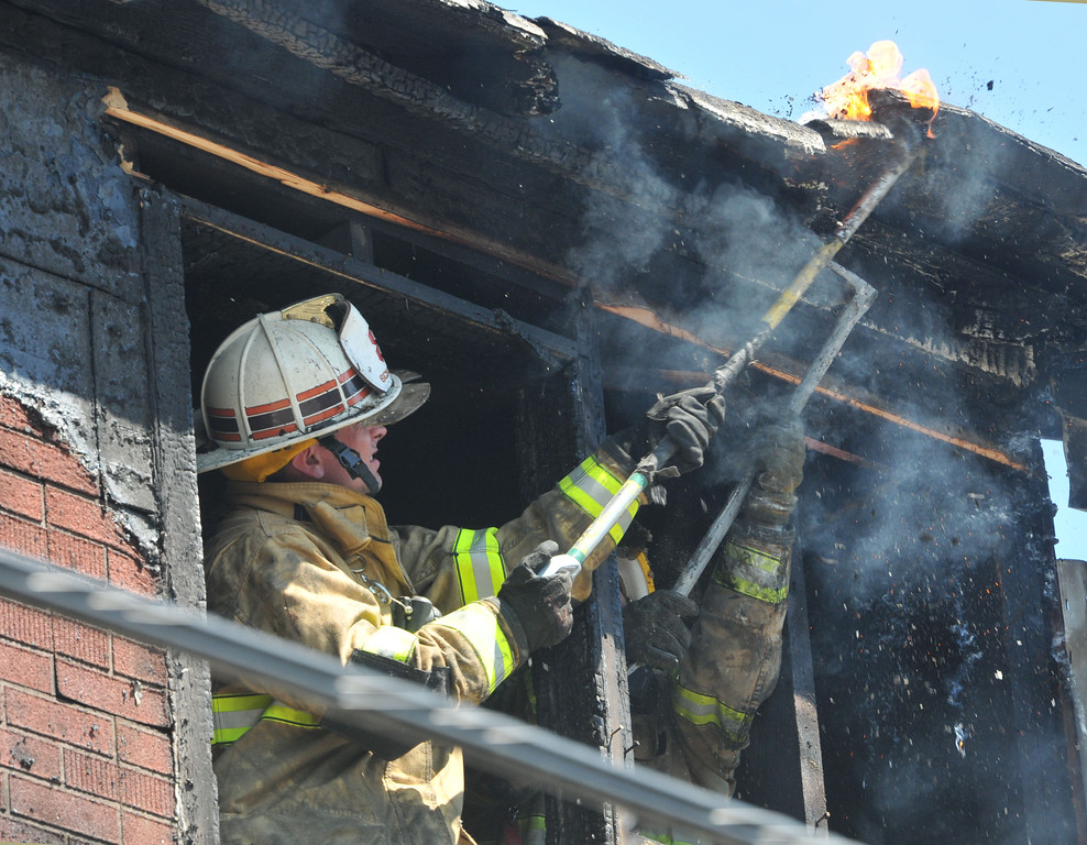 . PETE  BANNAN-DIGITAL FIRST MEDIA        Firefighters pull apart roofing material to reach fire at a house fire on the 600 block of Coates St. in Coatesville Monday morning.  Two unoccupied homes were seriously damaged in the two alarm fire.