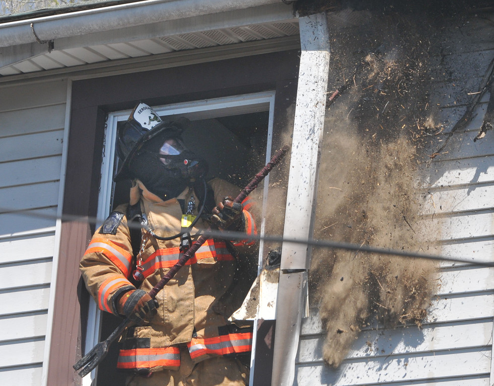 . PETE  BANNAN-DIGITAL FIRST MEDIA        A firefighter wearing breathing equipment pulls down insulation and roofing material as he searches for hidden fire at a house fire on the 600 block of Coates St. in Coatesville Monday morning.  Two unoccupied homes were seriously damaged in the two alarm fire.