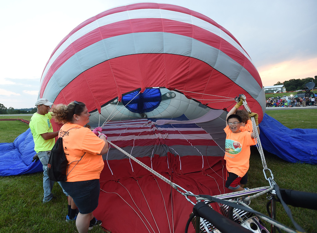 . PETE BANNAN-DIGITAL FIRST MEDIA  Volunteers assist  filling the USA Rocket at the Chester County Balloon Festival Friday evening Jun 24, 2016 at New Garden Airport. The event runs through Sunday.