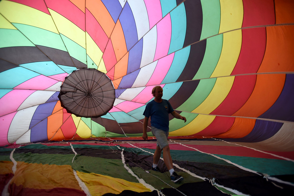 . PETE BANNAN-DIGITAL FIRST MEDIA  Anthony Seeger of Greensville, S Carolina walks through his balloon as it fills at the Chester County Balloon Festival Friday evening Jun 24, 2016 at New Garden Airport. The event runs through Sunday.