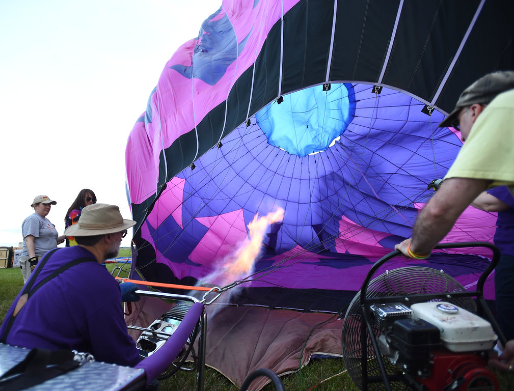 . PETE BANNAN-DIGITAL FIRST MEDIA   Keith Sproul, left, uses propane burners and ventilation fans to fill his balloon at the Chester County Balloon Festival Friday evening Jun 24, 2016 at New Garden Airport. The event runs through Sunday. Sproul is from New Brunswick, New Jersey.