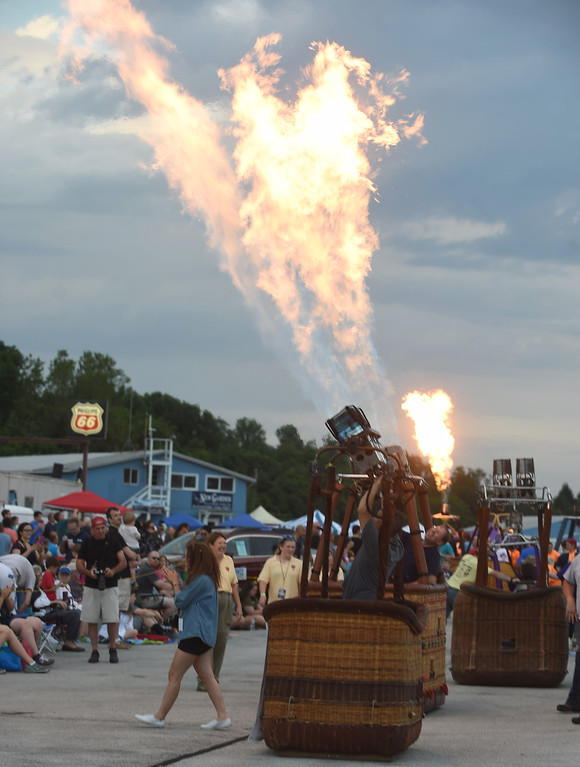 . PETE BANNAN-DIGITAL FIRST MEDIA  Balloonists fire their propane burners to entertain the crowd while waiting for the winds to die down at the Chester County Balloon Festival Friday evening Jun 24, 2016 at New Garden Airport. The event runs through Sunday.