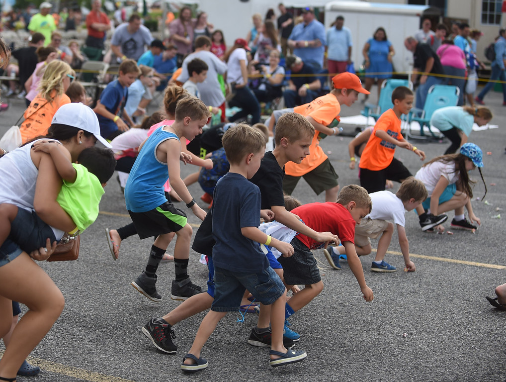 . PETE BANNAN-DIGITAL FIRST MEDIA  CHildren rush to pick u candy dropped from a romote controled plane at the Chester County Balloon Festival Friday evening Jun 24, 2016 at New Garden Airport. The event runs through Sunday.
