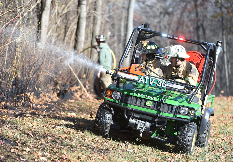 PETE  BANNAN-DIGITAL FIRST MEDIA    <br /> Firefighters use an ATV to control a wind whipped brush fire on Park Ave.in E. Fallowfield Township. Westwood Battalion chief John Sly said the fire covered approximately 2 1/2 acres.   It took crews from Westwood, Cochranville, Wagontown and Po-Mar-Lin ftwo hours to bring the fire under control and extinguish hotspots.