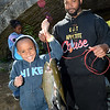 PETE BANNAN- DIGITAL FIRST MEDIA  Zakai Dickinson,6, and Dad Brandon of  Coatesville hold up their catch from  the first annual Coatesville fishing rodeo on the banks of the West Brandywine Creek at the Riverwalk Trail. City children fished for free.