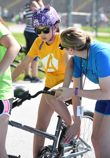 PETE BANNAN-DIGITAL FIRST MEDIA  Counselors assist Maddy Mau, 9, of West Windsor, NJ, as she prepares to ride the tandem bike ride at Camp Abilities at West Chester University. The camp, held over the Memorial Day weekend offers developmental sports for school-age children who have visual impairments including blindness or low vision.