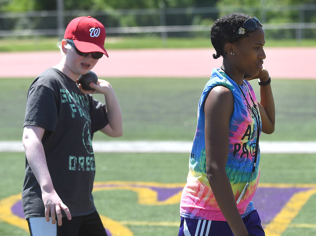 . PETE BANNAN-DIGITAL FIRST MEDIA  Volunteer Mim Hughes, right of Coatesville demonstrates the proper technique for throwing the shot put to Kate DuBois,14, of Arlington, VA. at Camp Abilities at West Chester University. The camp, held over the Memorial Day weekend offers developmental sports for school-age children who have visual impairments including blindness or low vision.