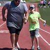 PETE BANNAN-DIGITAL FIRST MEDIA West Chester University senior, Drew FItzpatrick  aids Cam Friedrich,12, of Leesburg, VA. in the 4x100 at Camp Abilities at West Chester University. The camp, held over the Memorial Day weekend offers developmental sports for school-age children who have visual impairments including blindness or low vision.