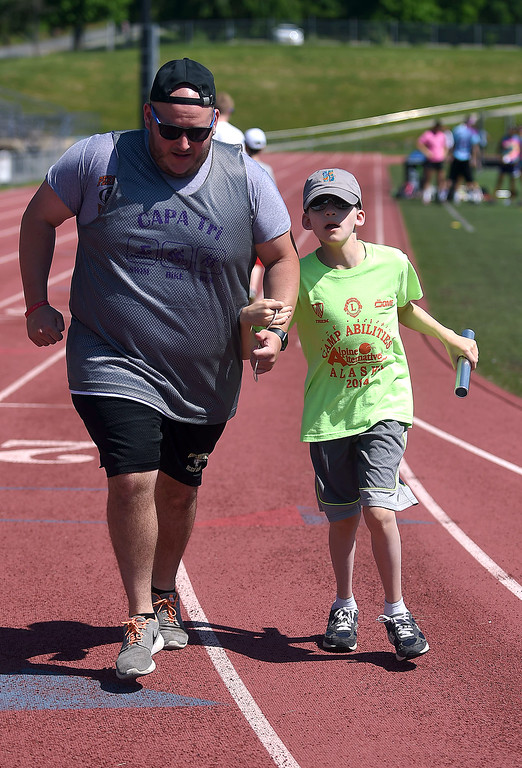 . PETE BANNAN-DIGITAL FIRST MEDIA West Chester University senior, Drew FItzpatrick  aids Cam Friedrich,12, of Leesburg, VA. in the 4x100 at Camp Abilities at West Chester University. The camp, held over the Memorial Day weekend offers developmental sports for school-age children who have visual impairments including blindness or low vision.