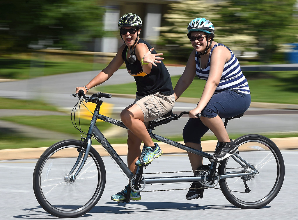 . PETE BANNAN-DIGITAL FIRST MEDIA  Volunteer Beth Foster and  camper Lexi Deel,15, of New Castle ,enjoy the tandem bike ride at Camp Abilities at West Chester University. The camp, held over the Memorial Day weekend offers developmental sports for school-age children who have visual impairments including blindness or low vision.