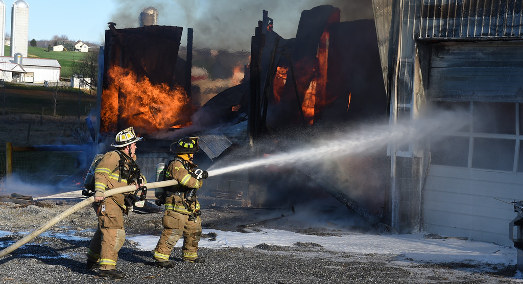 . VINNY TENNIS - Daily Local News  Firefighters from three counties, Lancaster, Chester, and Berks,  work on the scene of a fire that destroyed a woodworking shop and a clock shop in the 2400 block of Conestoga Creek Road in Caernarvon Twp, Lancaster County on Tuesday, Jan. 5, 2016.