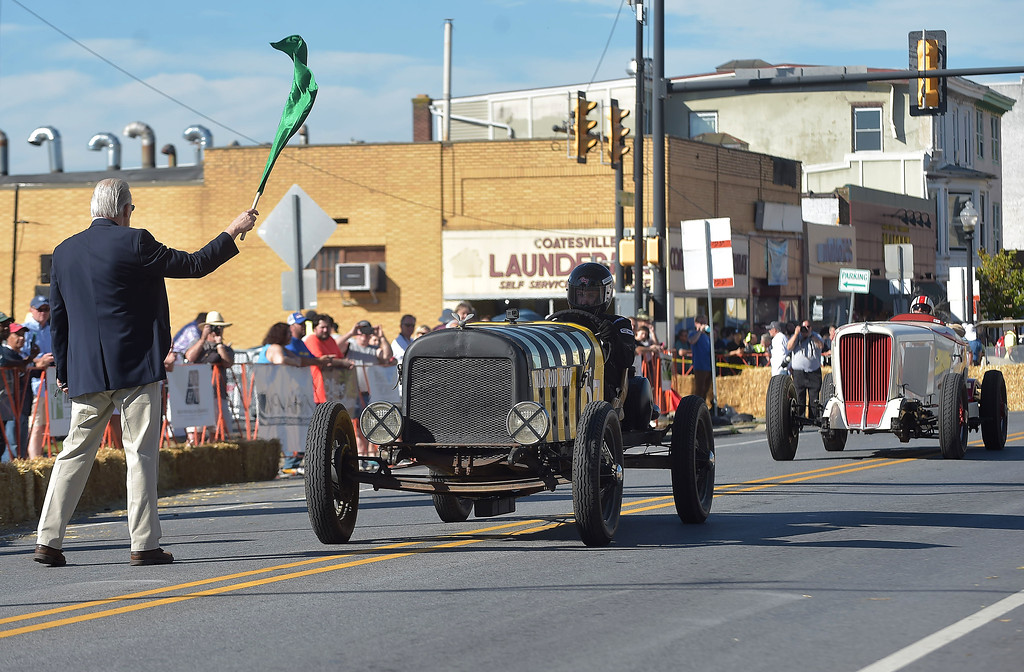 . PETE  BANNAN-DIGITAL FIRST MEDIA   Starter Paul Johnston waves the green flag for the the open wheeled section of the second Annual Coatesville Invitational Vintage Grand Prix Saturday Sept.23, 2017. Over 50 cars took part in  the day long timed races.