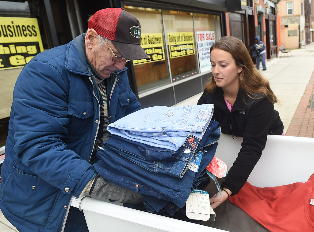 . PETE  BANNAN-DIGITAL FIRST MEDIA   Horton Gettz of Downingtown carries clothing to Samantha Turner from the Coatesville Army & Navy store as part of leftover inventory that the store sold them at a reduced price so they can distribute in to the Coatesville VA and to youth groups.