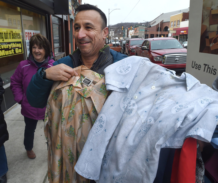 . PETE  BANNAN-DIGITAL FIRST MEDIA   TOm Bucci admires some of the clothing from the Coatesville Army & Navy store leftover inventory that the store sold  at a reduced price to distribute in to the Coatesville VA and to youth groups.