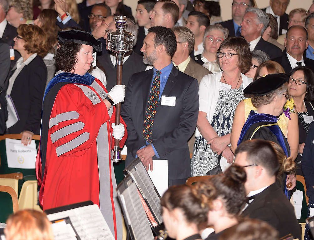 . PETE  BANNAN-DIGITAL FIRST MEDIA       Dr. Corinne Murphy carries the Mace into Emilie K. Asplundh Concert Hall. for the inauguration of West Chester University President Christopher Fiorentino Friday morning.    The mace has a history as a symbol of authority in civil and academic processions. Now ceremonial, the mace was originally a formidable weapon held ready to protect the dignitary in a procession.